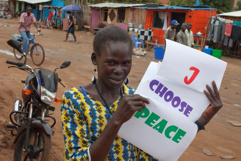 A young South Sudanese woman holds a sign stating