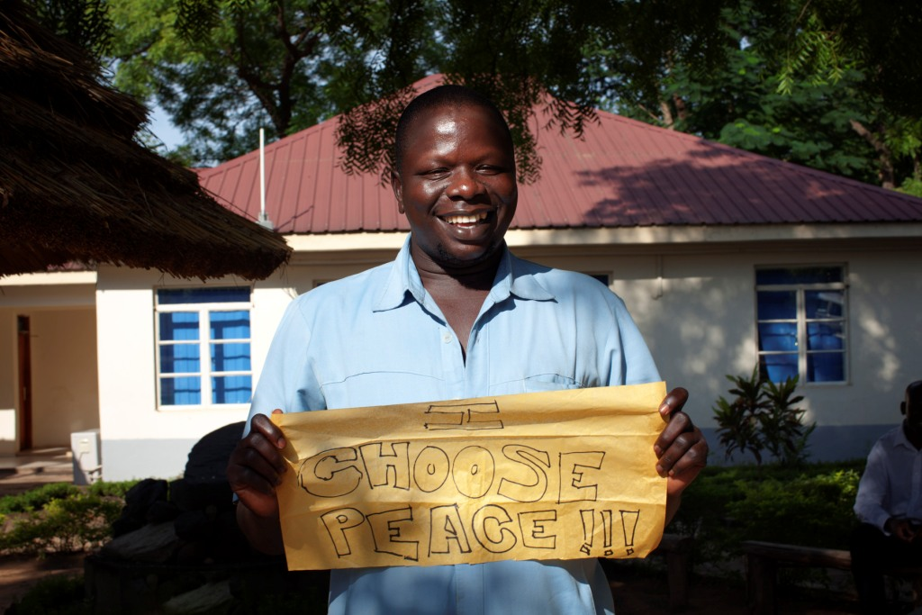 A South Sudanese man holds a sign stating
