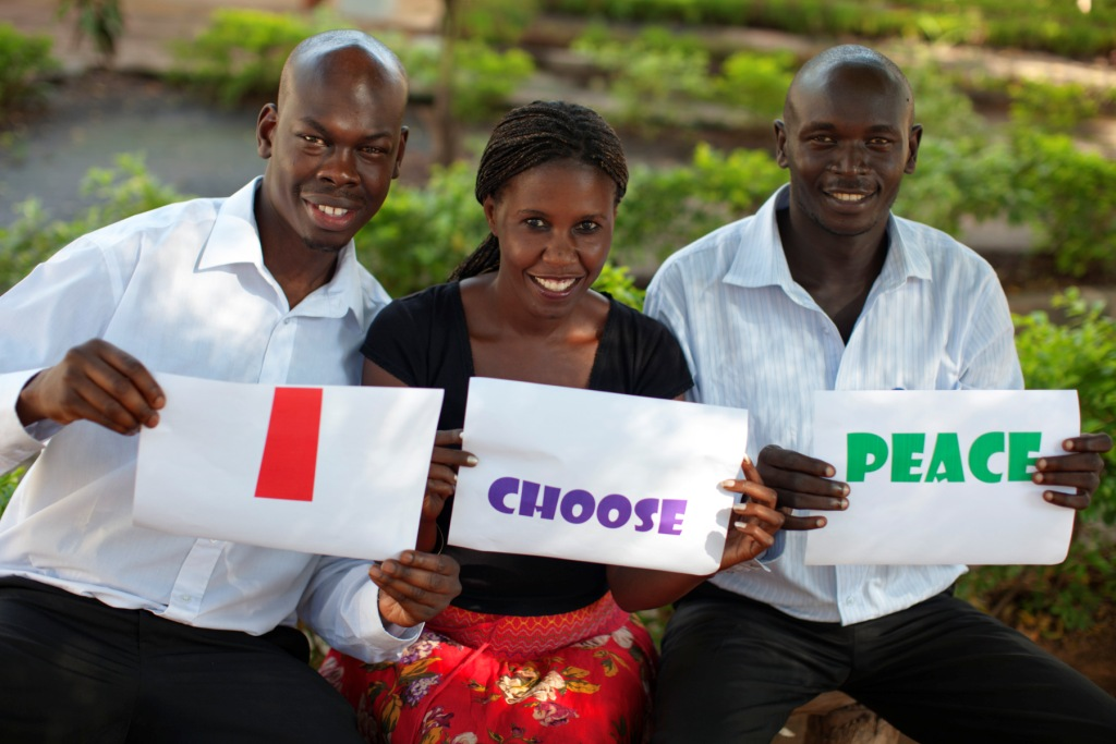 Three young South Sudanese professional holds a sign stating