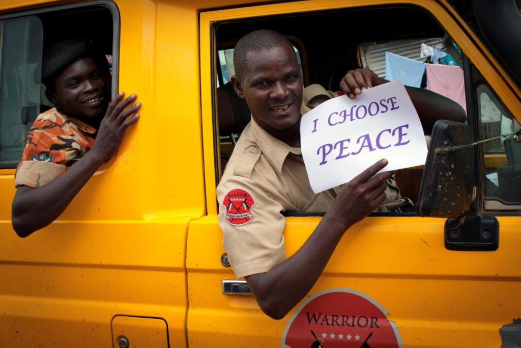 A private security guard (right) and member of South Sudan\'s security force (left) holds a sign stating