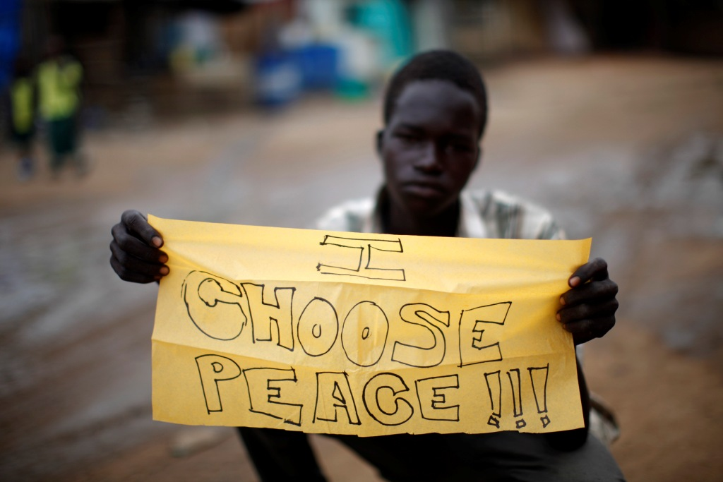 A young South Sudanese boy who works cleaning shoes in the streets holds a sign stating